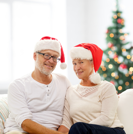 family, holidays, christmas, age and people concept - happy senior couple in santa helper hats sitting on sofa over living room and christmas tree background photo