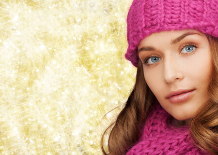 yellow fleece: happiness, winter holidays, christmas and people concept - close up of smiling young woman in pink hat and scarf over yellow lights background