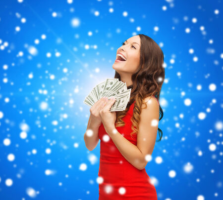 christmas profits: christmas, holidays, sale, banking and people concept - smiling woman in red dress with us dollar money over blue snowy background