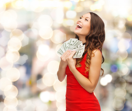 holiday profits: smiling woman in red dress with us dollar money over lights background