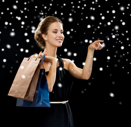 holydays: luxury, holydays, people and sale concept - smiling woman with shopping bags over black snowy background