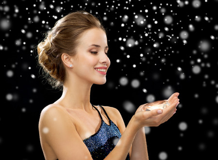 people, holidays, christmas and glamour concept - smiling woman in evening dress with diamond over black snowy background photo