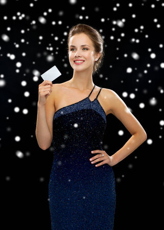 woman holding money: shopping, money, winter holidays, christmas and people concept - smiling woman in evening dress holding credit card over black snowy background