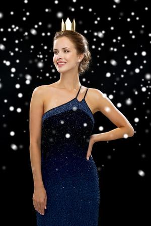 christmas crown: las personas, las vacaciones, la realeza y el concepto de Navidad - mujer sonriente en vestido de noche con la corona de oro sobre fondo cubierto de nieve negro
