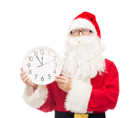 twelve month old: christmas, holidays and people concept - man in costume of santa claus with clock showing twelve