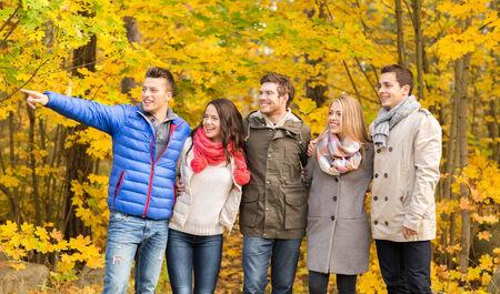 romantic couples: amor, las relaciones, la temporada, la amistad y la gente concepto - grupo de sonrientes hombres y mujeres que abrazan en parque del oto�o Foto de archivo