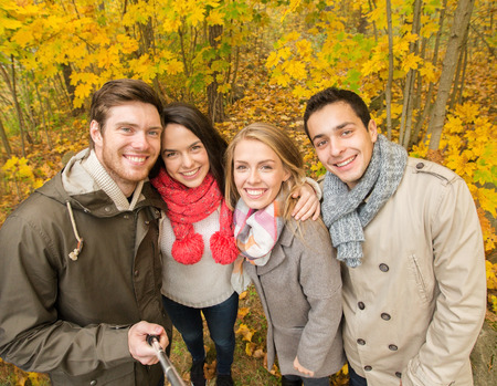 sticks: season, people, technology and friendship concept - group of smiling friends with smartphone or digital camera and selfie stick taking picture in autumn park
