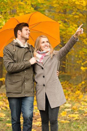 couple nature: love, season, family, gesture and people concept - smiling couple with umbrella walking and pointing finger in autumn park