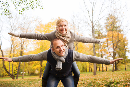 love, relationship, family and people concept - smiling couple having fun in autumn park photo