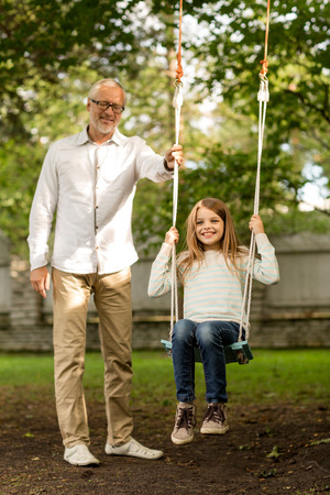 granddaughter:  happy grandfather and  granddaughter swinging on teeterboard outdoors Stock Photo