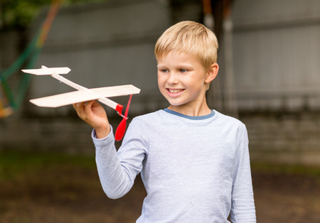 smiling little boy holding wooden airplane model in his hand outdoors photo