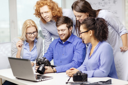 smiling creative team with laptop computer and photocameras working in office photo