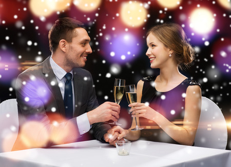 smiling couple clinking glasses of sparkling wine at restaurant over night lights background photo