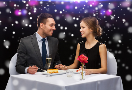 candle light dinner: smiling couple eating dessert at restaurant over night lights background