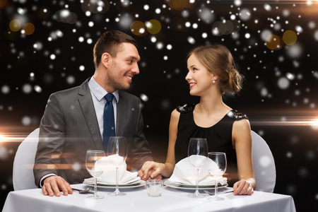 couple dining: smiling couple at restaurant over night lights background