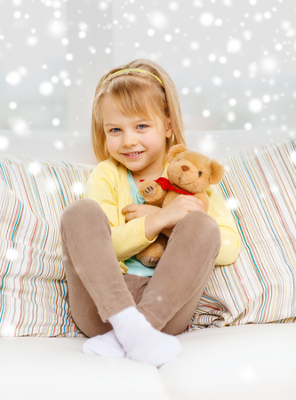 hollidays: smiling little girl with teddy bear sitting on sofa at home