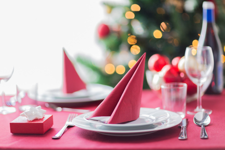 holidays, celebration and home concept - close up of room with christmas tree and decorated table photo