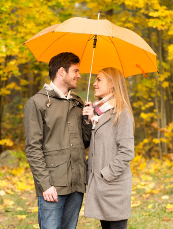 embracing couple: love, relationship, season, family and people concept - smiling couple with umbrella walking in autumn park