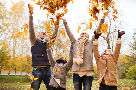 preteen boys: family, childhood, season and people concept - happy family playing with autumn leaves in park