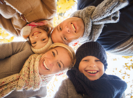 autumn family: family, childhood, season and people concept - happy family in autumn park Stock Photo
