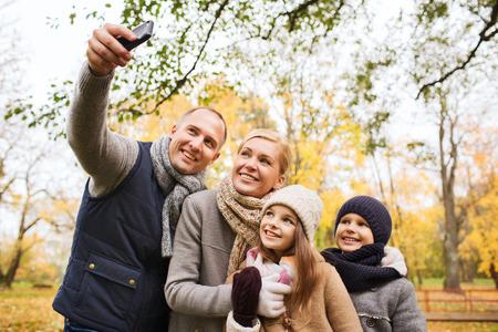 mama e hijo: la familia, la infancia, la estaci�n, la tecnolog�a y el concepto de la gente - familia feliz teniendo Autofoto con smartphone en el Parque de oto�o