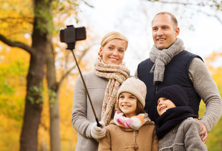 to stick: family, childhood, season, technology and people concept - happy family photographing with smartphone and selfie stick in autumn park