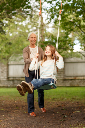 family, happiness, generation, home and people concept - happy grandmother and granddaughter swinging on teeterboard outdoors photo