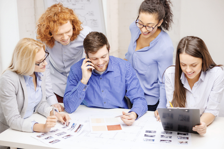 business, office, technology and startup concept - creative team with papers and clipboard working at office photo