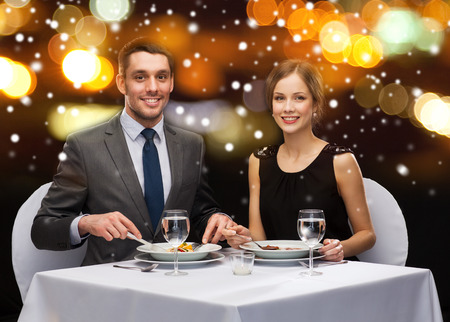 main course: food, christmas, holidays and people concept - smiling couple eating main course at restaurant over night lights background