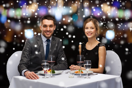 main course: restaurant, christmas, holidays and people concept - smiling couple eating main course at restaurant over night lights background