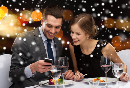 technology, food, christmas, holidays and people concept - smiling couple with smartphone eating at restaurant over night lights background photo