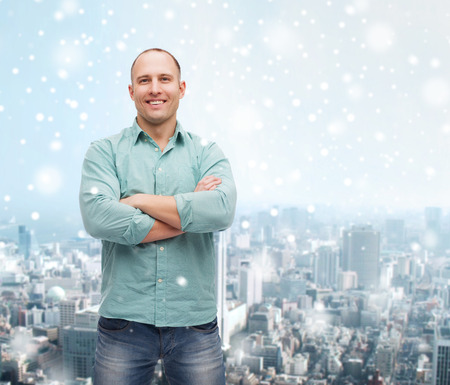 mani incrociate: happiness and people concept - smiling man with crossed arms standing over snow and city background