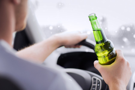 drunk driving: transportation, alcohol, vehicle and people concept - close up of man drinking alcohol while driving car Stock Photo