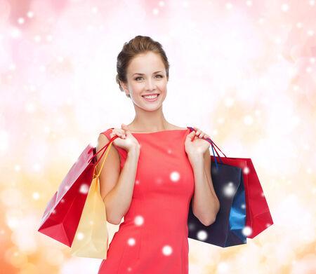 la compra, venta, Navidad y concepto de vacaciones - sonriente mujer elegante en un vestido rojo con bolsas de compra sobre fondo de color rosa cubierto de nieve