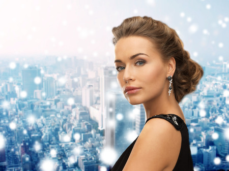 people, holidays, christmas and glamour concept - beautiful woman in evening dress wearing earrings over snowy background Imagens