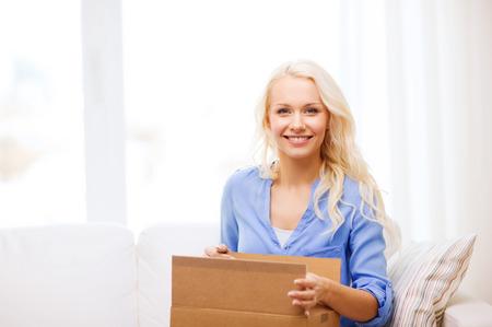 transport, post en mensen concept - lachende jonge vrouw het openen van kartonnen doos thuis