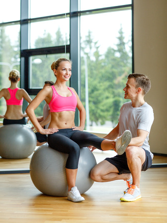 sport, fitness, lifestyle and people concept - smiling man and woman with exercise ball in gym photo