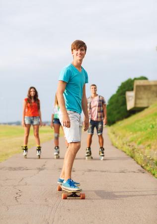休日、休暇、愛と友情の概念 - ローラー スケート、スケート ボード屋外に乗って笑顔ティーンエイ ジャーのグループ 写真素材