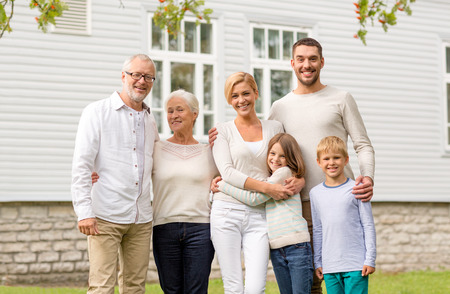 family, happiness, generation, home and people concept - happy family standing in front of house outdoors Imagens