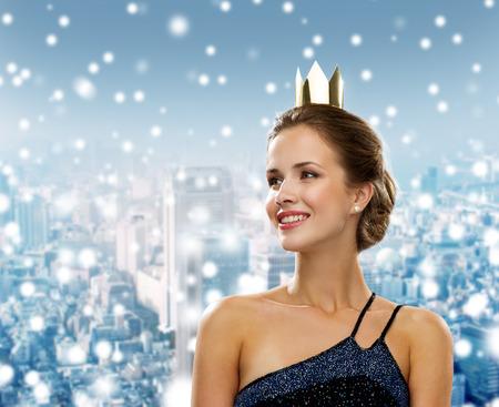 christmas crown: las personas, las vacaciones, la realeza y el concepto de Navidad - mujer sonriente en vestido de noche con la corona de oro sobre fondo cubierto de nieve ciudad