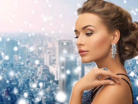people, holidays, christmas and glamour concept - beautiful woman in evening dress wearing ring and earrings over snowy city background Фото со стока