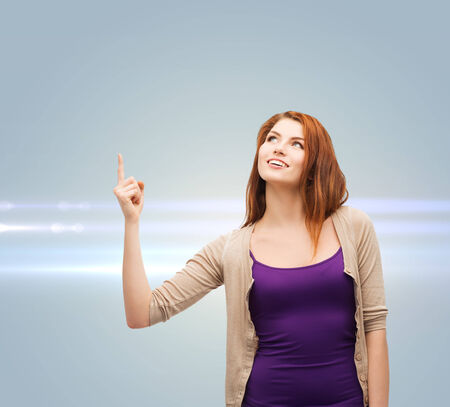 future, gesture and people concept - smiling teenage girl in casual clothes pointing finger up over gray background with laser light photo