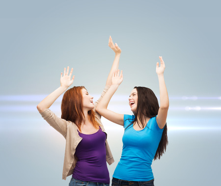 happiness, friendship and people concept - smiling teenage girls having fun over gray background with laser light photo