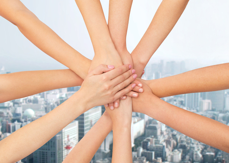 healthcare, people, gesture and medicine concept - close up of women hands on top of each other over city background Stock Photo