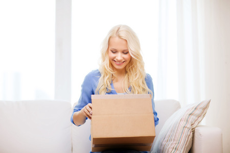 package: transportation, post and people concept - smiling young woman opening cardboard box at home