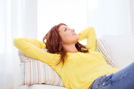 to think: home and happiness concept - smiling young woman lying on sofa at home