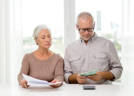 가족, 저축, 나이 및 사람들이 개념 - 수석 몇 서류, 돈 및 계산기 집에서