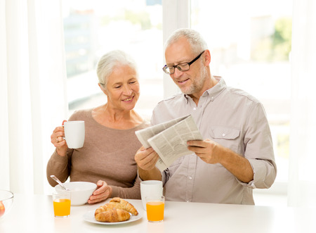 family, technology, food, drinks and people concept - happy senior couple having breakfast and reading newspaper at home photo