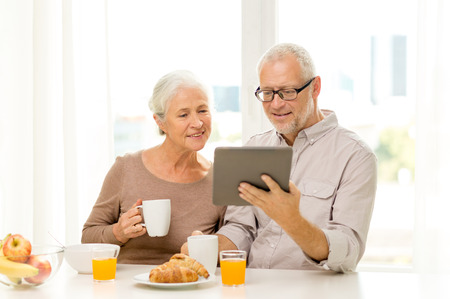 family, technology, food, drinks and people concept - happy senior couple with tablet pc computer having breakfast at home photo