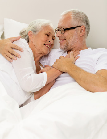 wife: family, bedtime, resting, age and people concept - happy senior coupler lying in bad at home Stock Photo